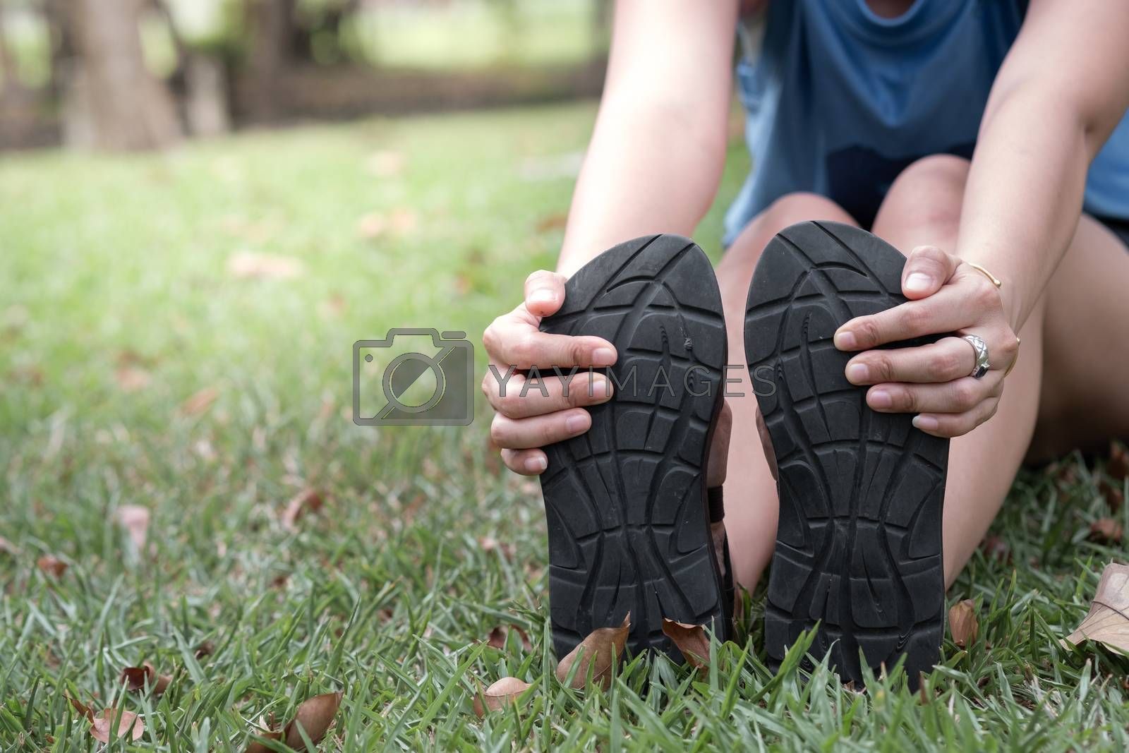 Hand of woman holding her feet and stretch the muscles in the park.