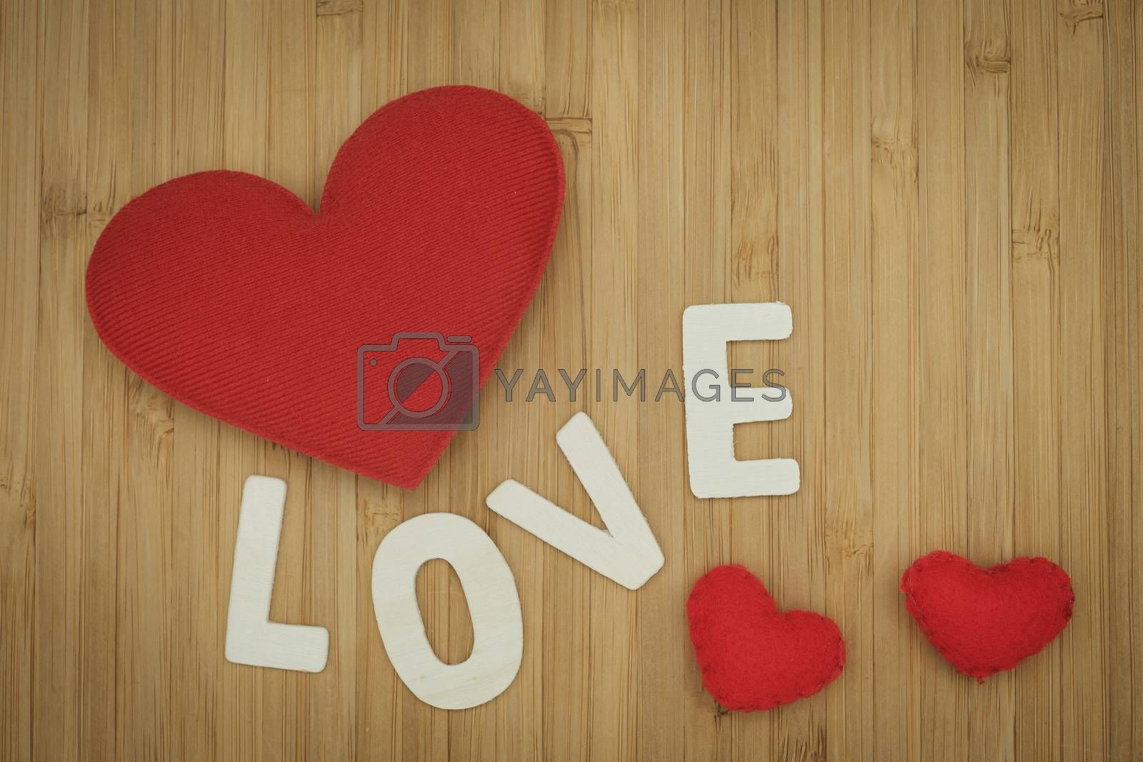 Red pillow heart and love word on wooden  background. Valentine concept Vintage tone.