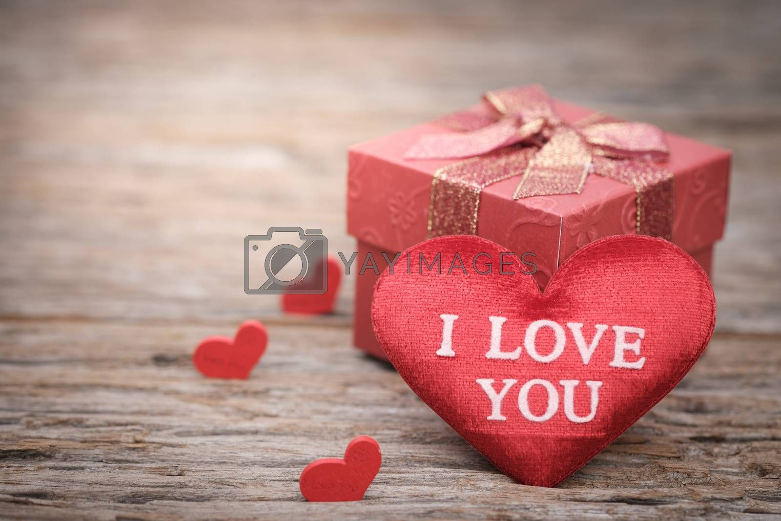 Red pillow heart shape and gift box on wooden background with space to write. Valentine concept, Vintage tone, AF point selection.