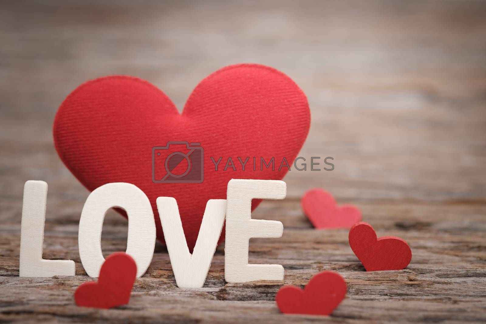 Red pillow heart shape and love word on wooden background with space to write. Valentine concept, Vintage tone, AF point selection.