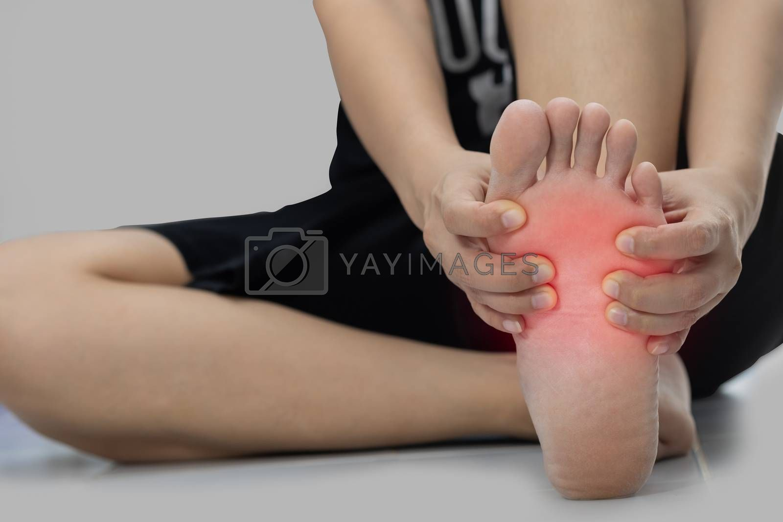 Woman sitting on the floor Her hand caught at the foot pain.