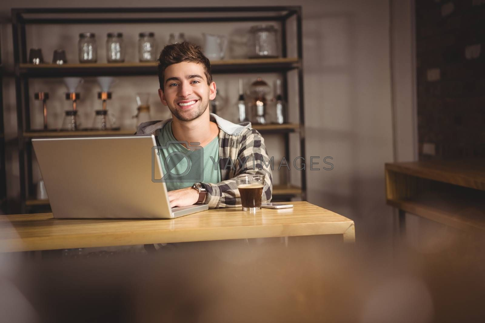 Portrait of smiling hipster sitting and using laptop at coffee shop