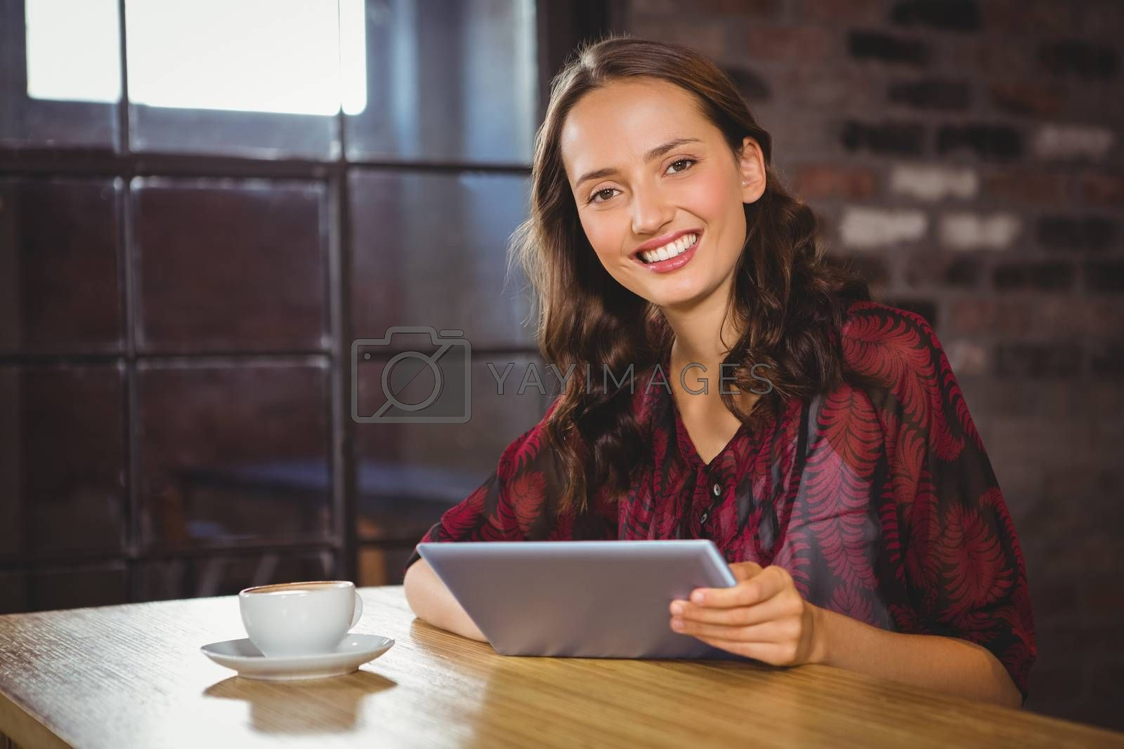 Portrait of smiling brunette having coffee and holding tablet at coffee shop