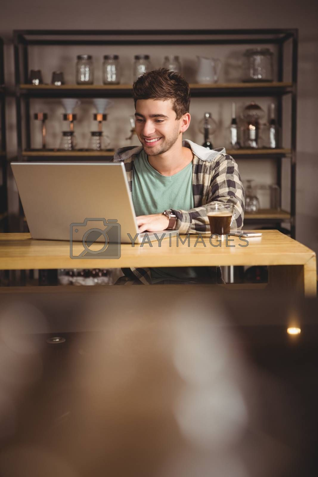 Smiling hipster sitting and using laptop at coffee shop