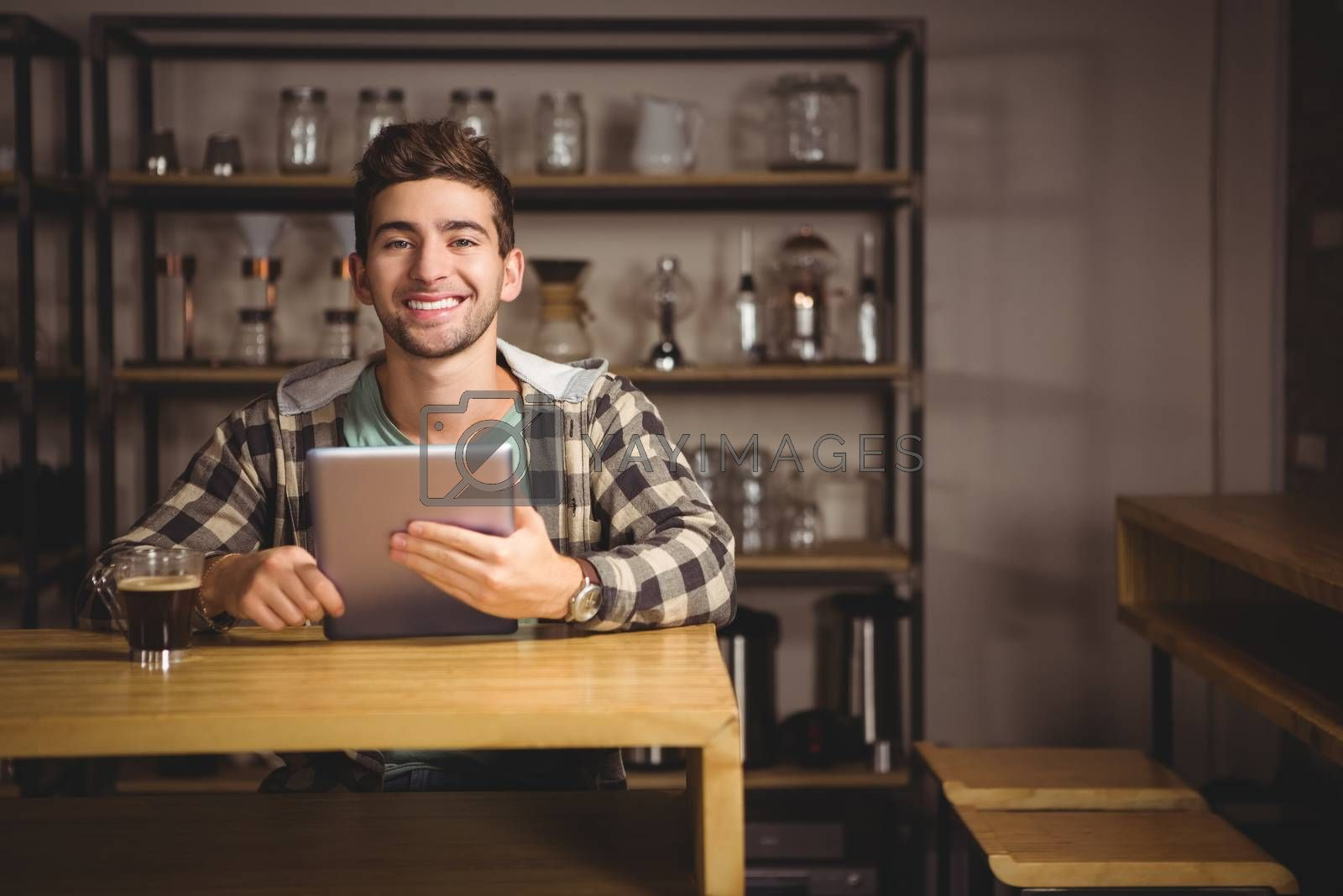 Portrait of smiling hipster having coffee and holding tablet computer at coffee shop