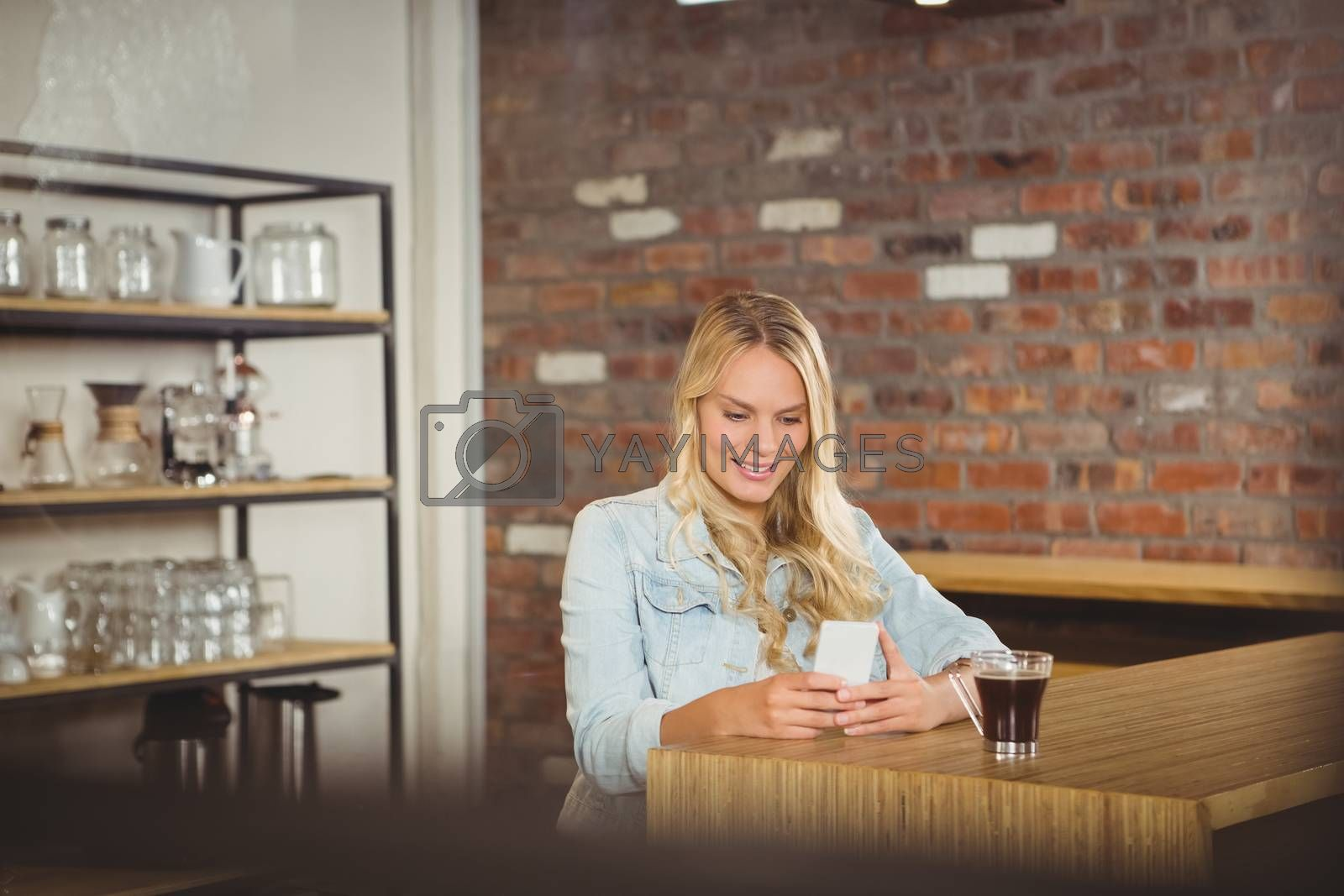 Smiling blonde having coffee and using smartphone at coffee shop