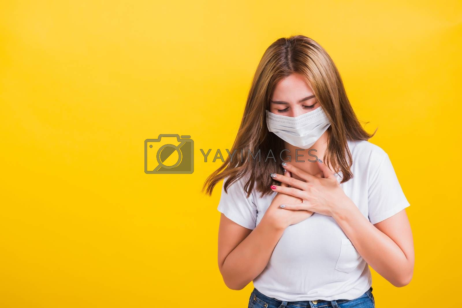 Asian portrait beautiful cute young woman standing wear t-shirt cough in mask protection from COVID virus epidemic or air pollution isolated, studio shot on yellow background with copy space