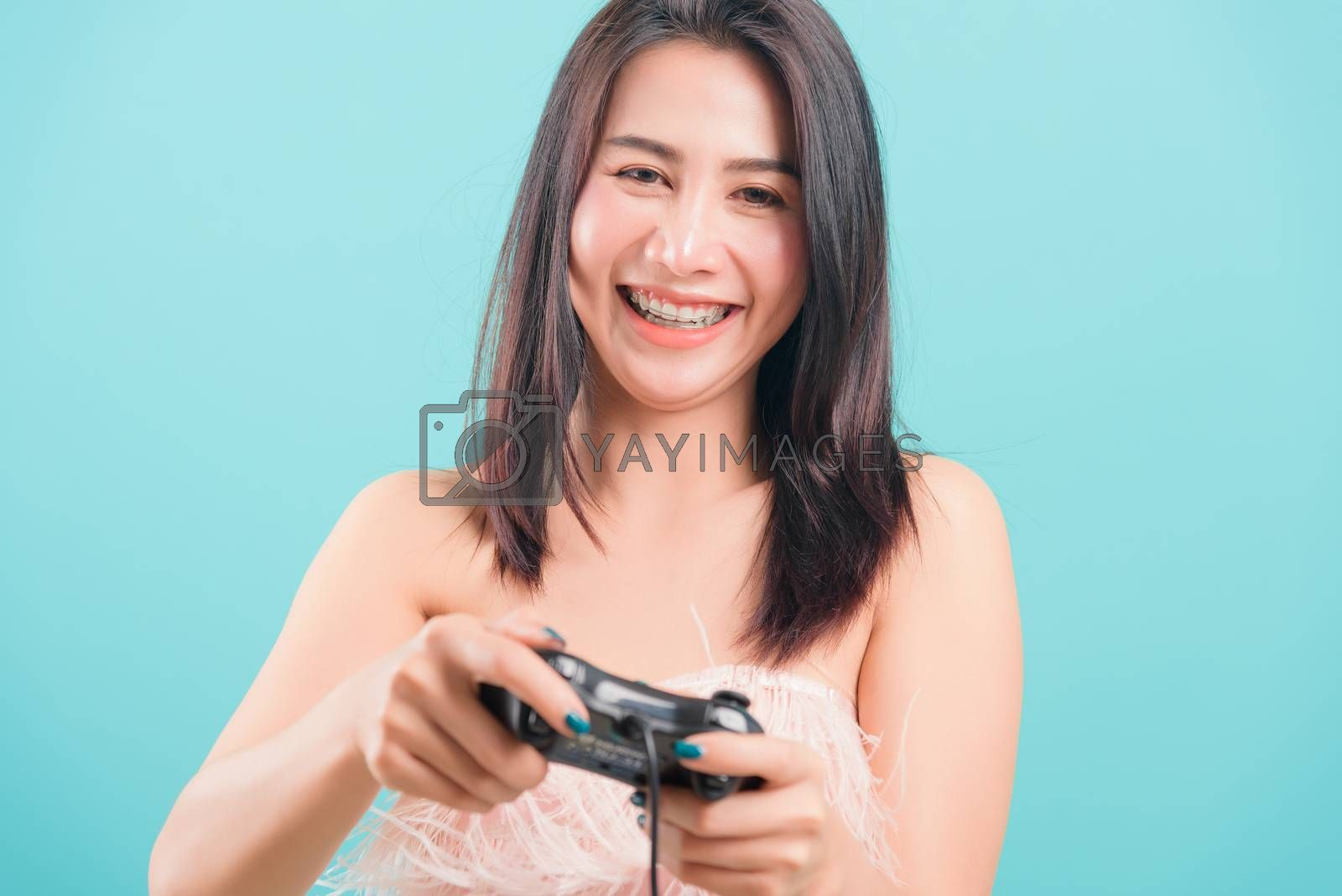 Asian happy portrait beautiful young woman standing smile lifestyle games technology her holding joystick game playing on-hands on blue background with copy space for text