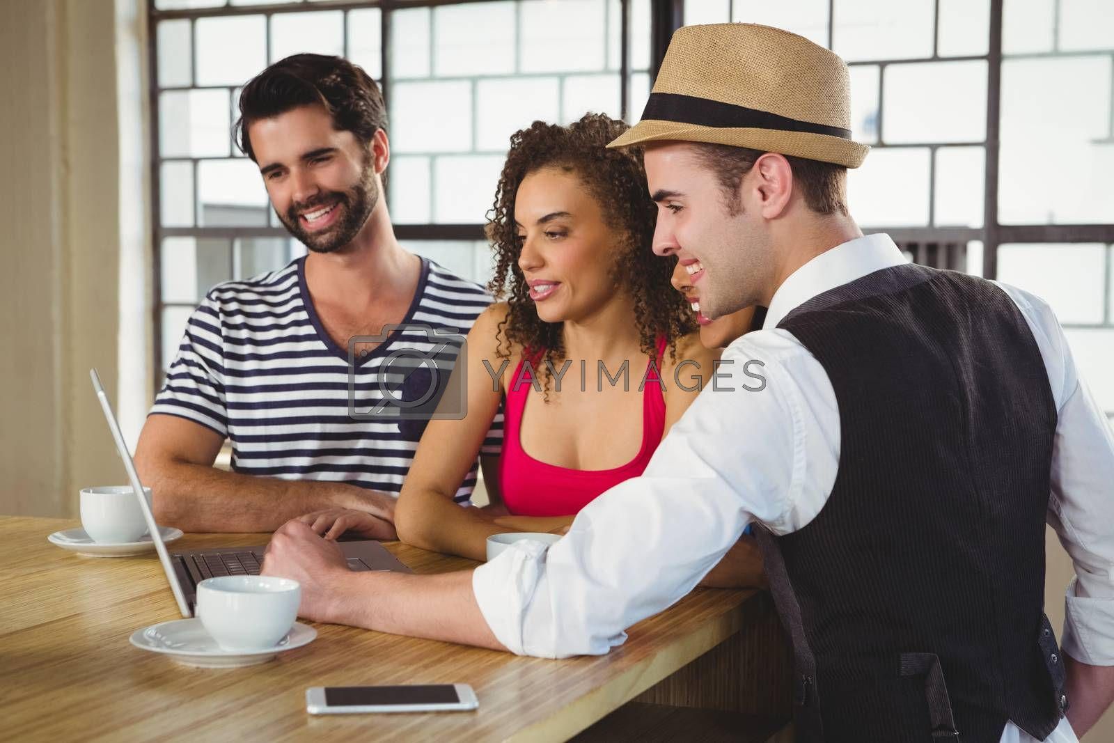 Smiling friends looking at laptop and having coffee at coffee shop
