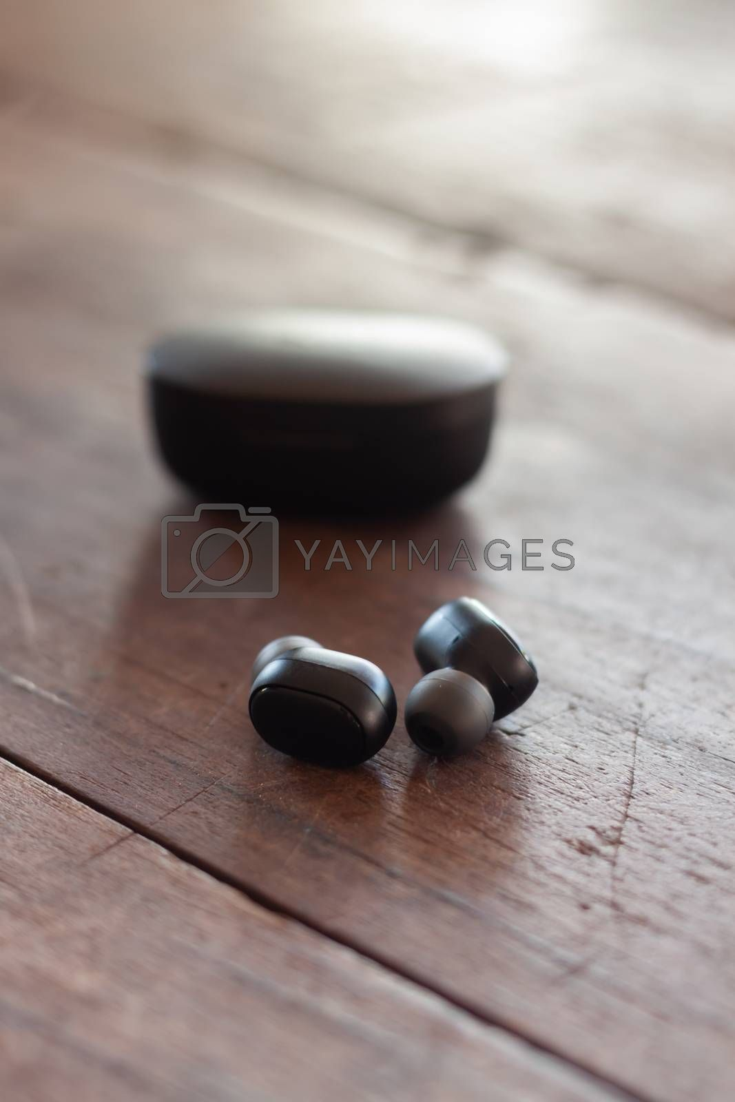 Wireless headphones on wooden background, stock photo