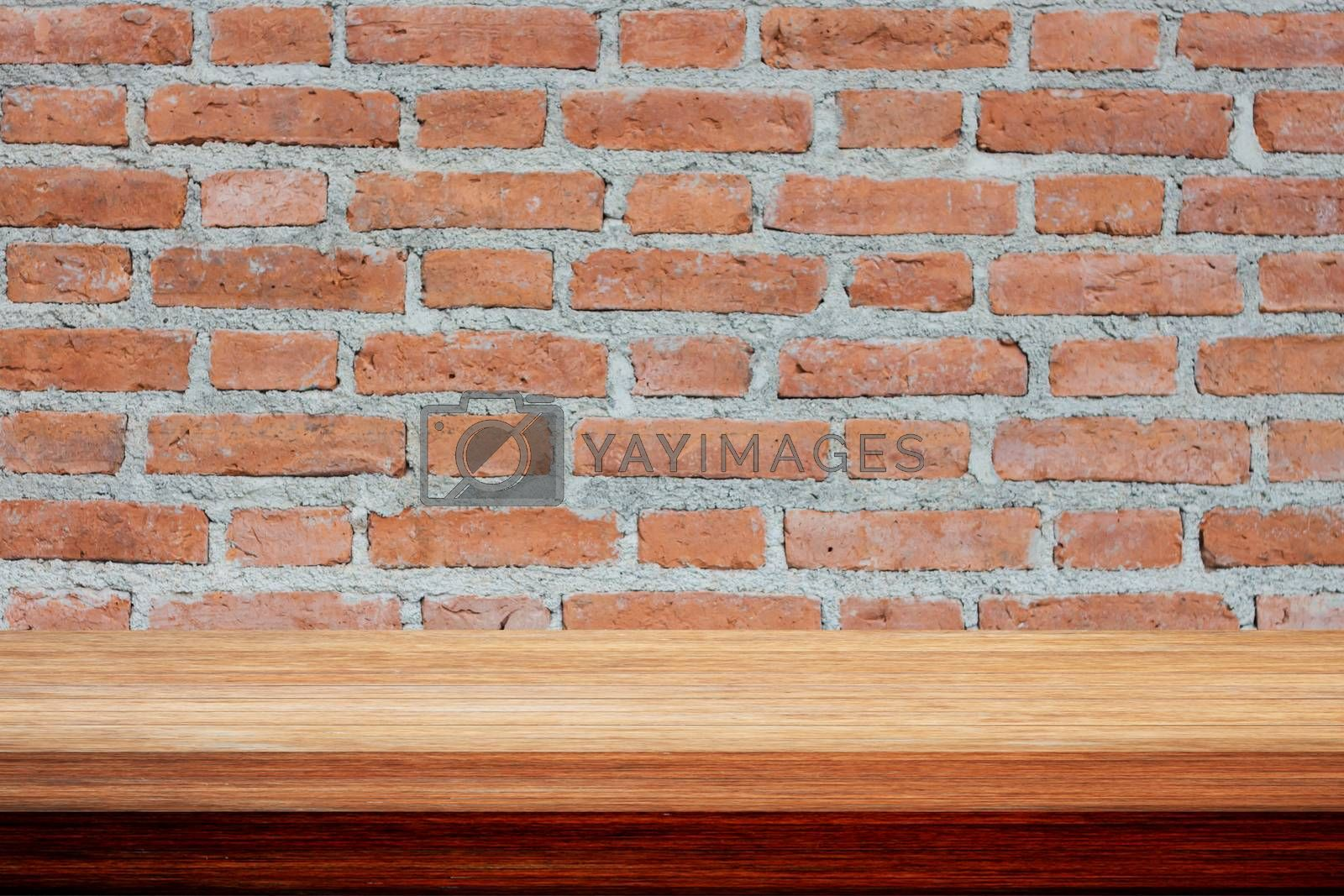 Old wooden table on brick wall, stock photo