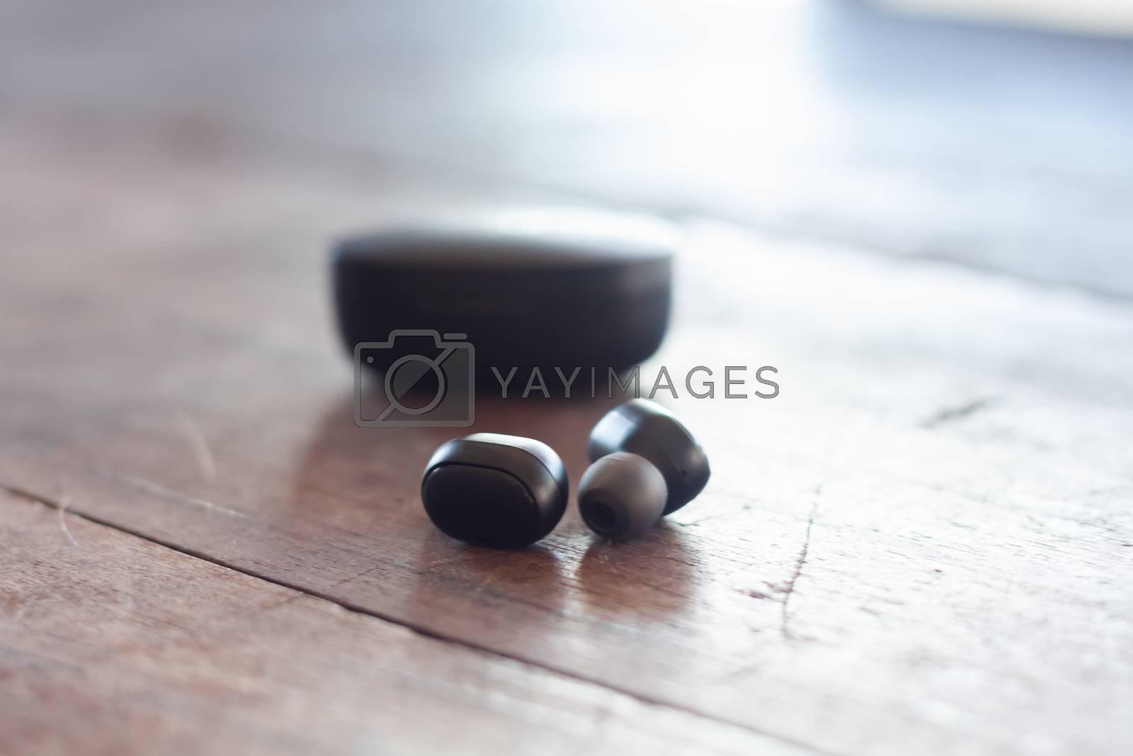 Wireless headphones on wooden background, stock photo