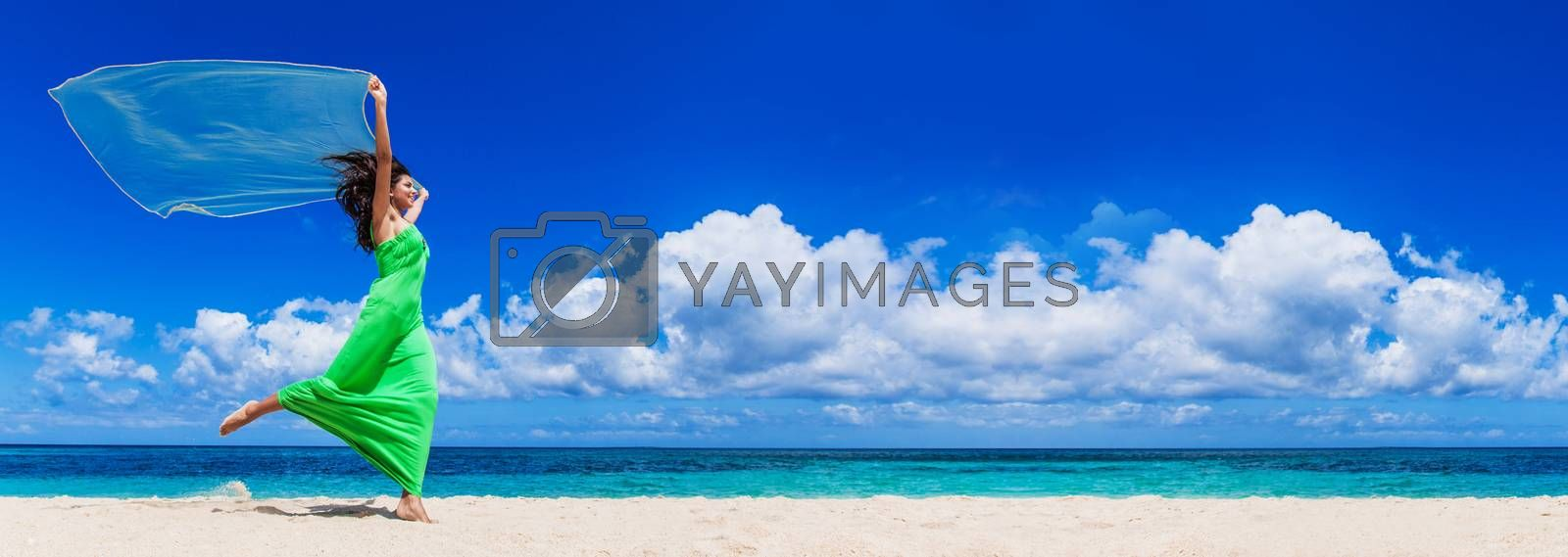 Female model in long green dress run on beach waving white fabric, vacation, freedom concept