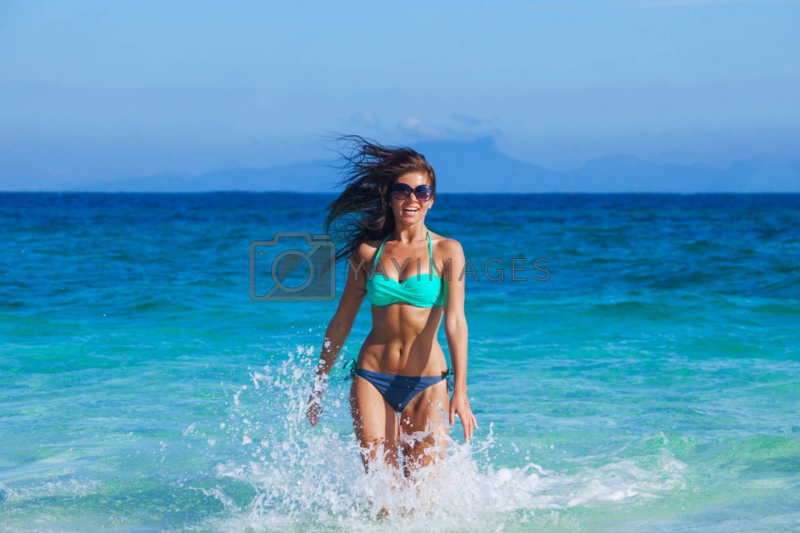 Beautiful happy girl in bikini and sunglasses running in tropical sea waves