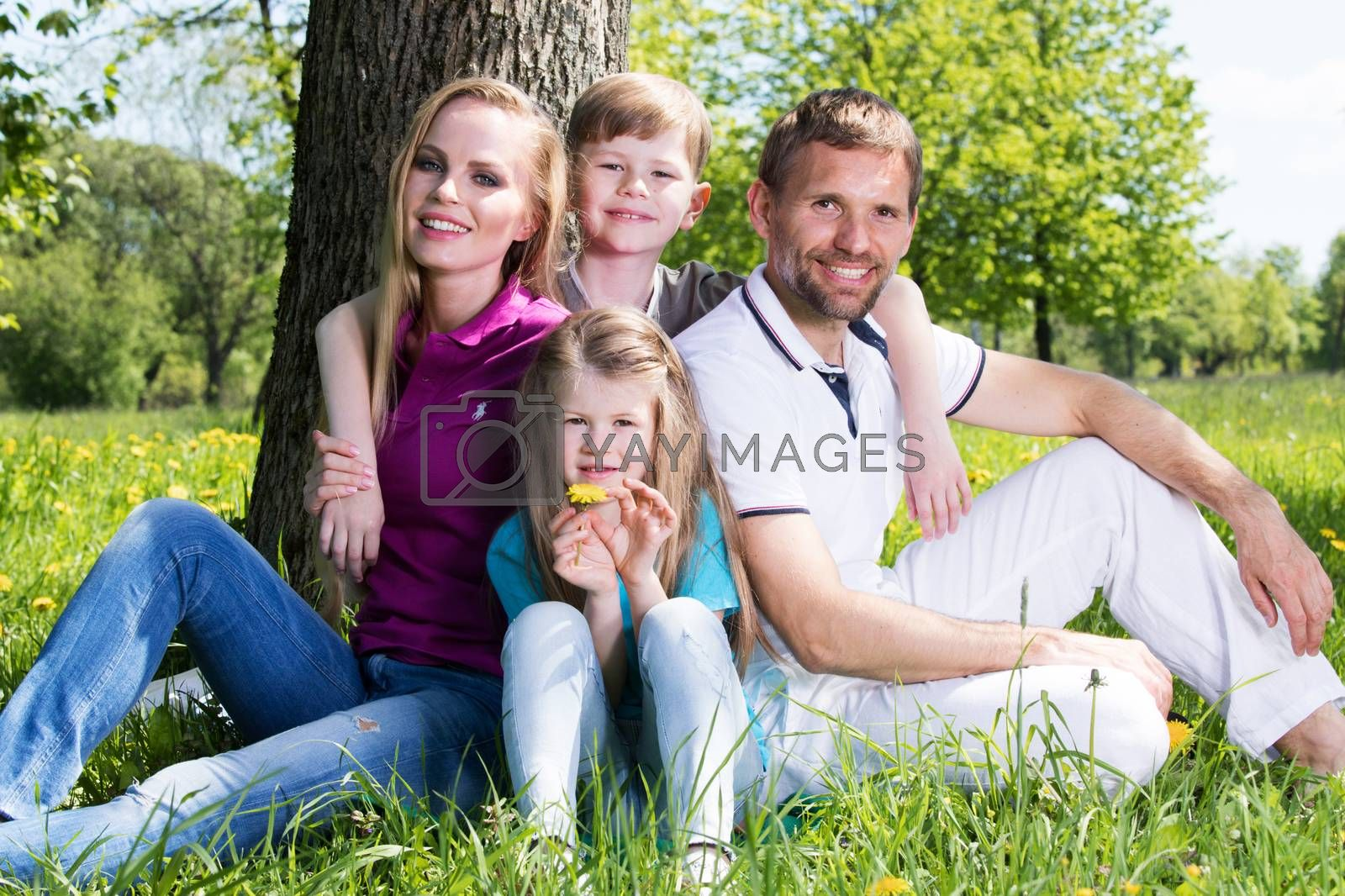 Happy family of parents and two children sitting on grass in spring park