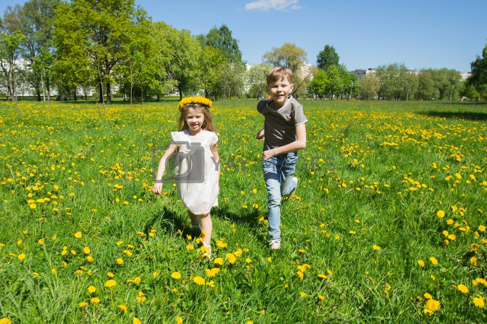 Young boy and girl brither and sister running in a sunny meadow with dandelion flowers family fun concept