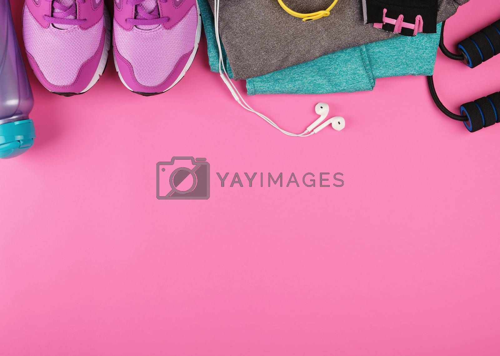pink women's sneakers, a bottle of water, gloves and a jump rope for sports on a pink background, top view, copy space, flat lay