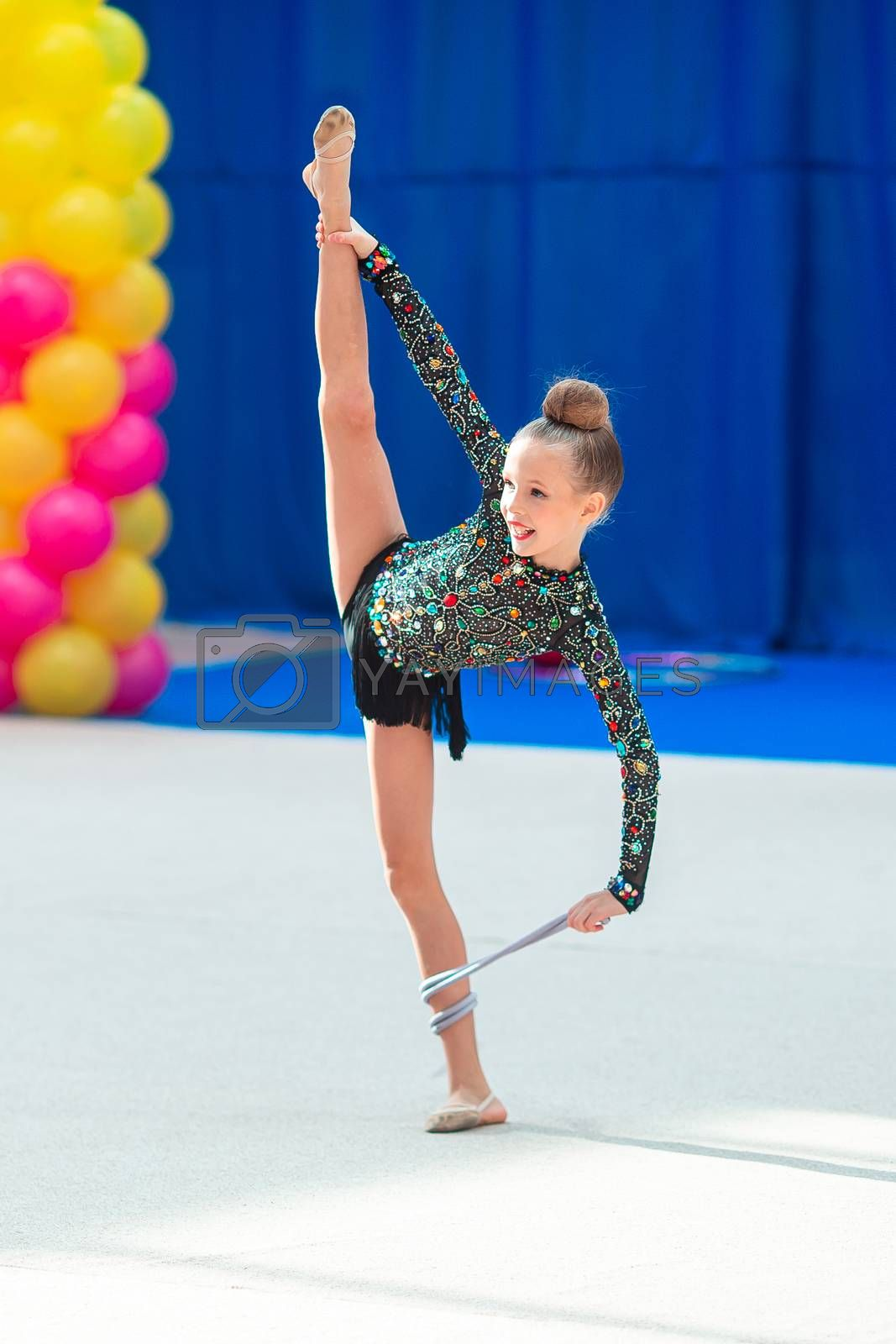 Beautiful little girl gymnast performs in competitions with rope