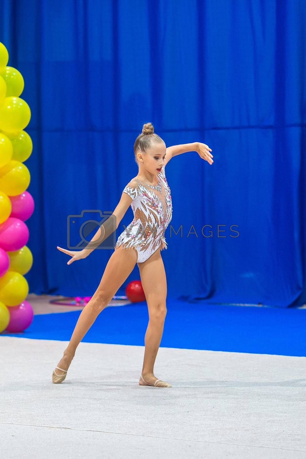 Beautiful little girl gymnast performs in competitions