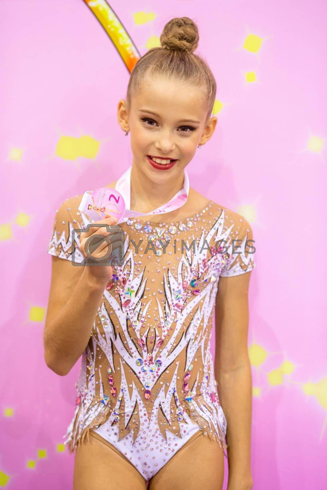 Little gymnast with her sports awards a cup and a medal on the carpet in rhythmic gymnastics