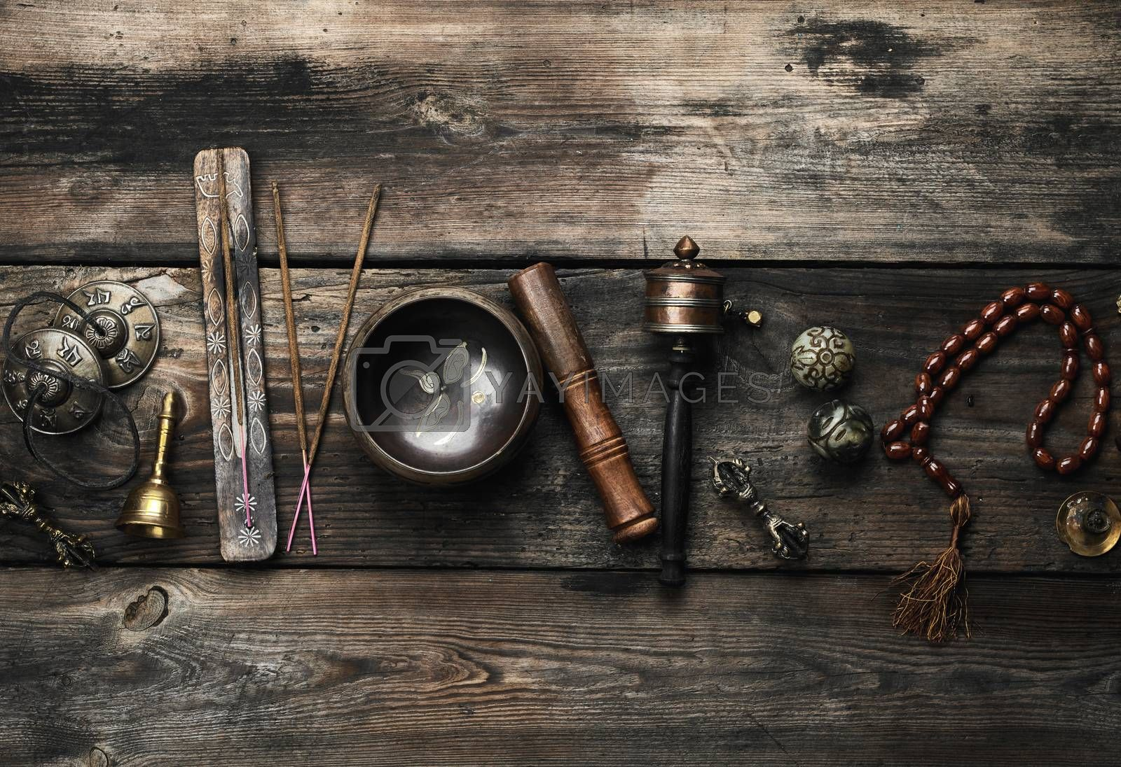Copper singing bowl, prayer beads, prayer drum and other Tibetan religious objects for meditation and alternative medicine on a brown wooden background, copy space