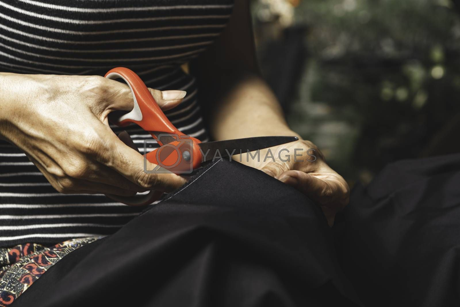 Woman cutting black fabric with scissors. Housework and lifestyle concept.