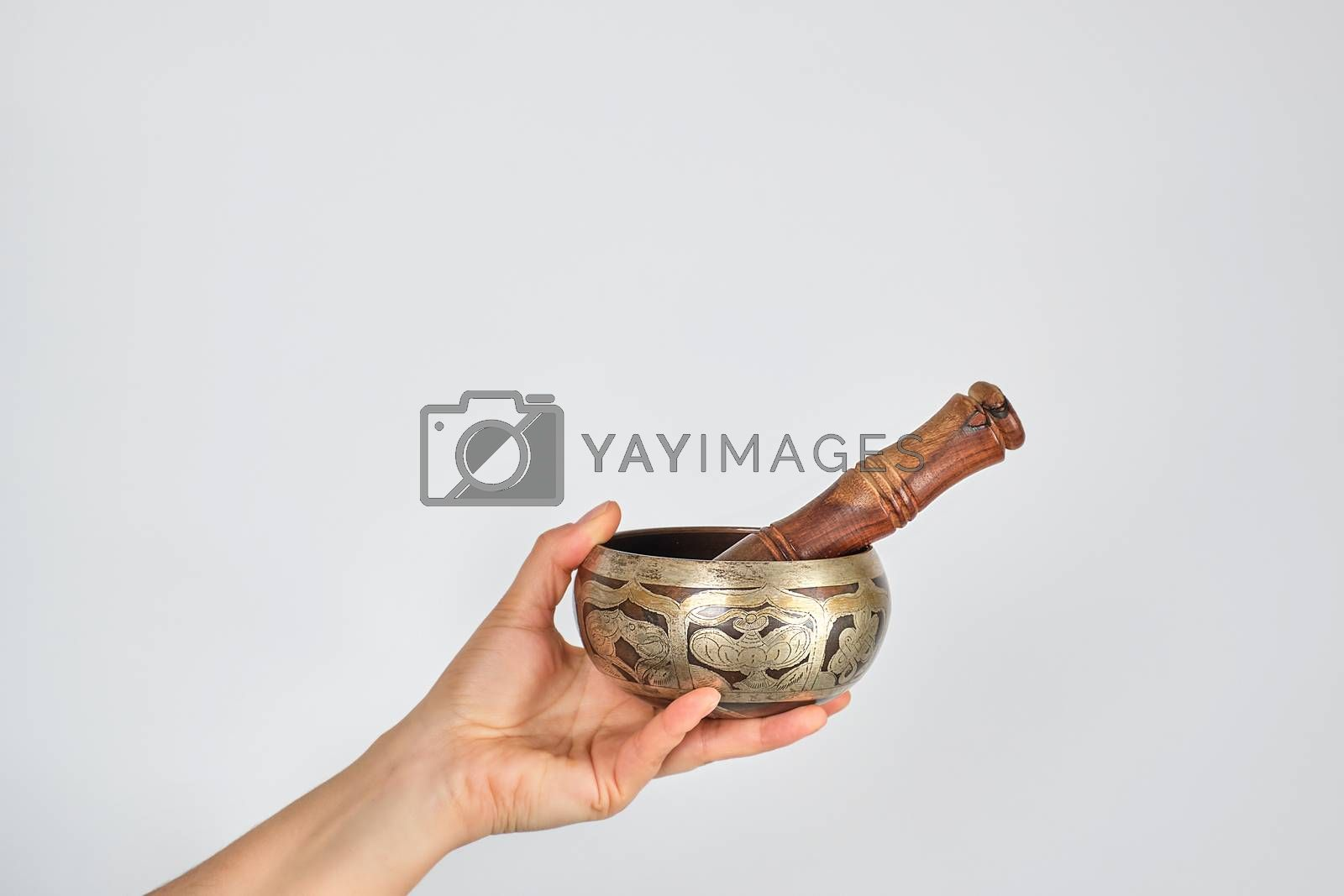 copper singing bowl and wooden stick in female hand  by ndanko