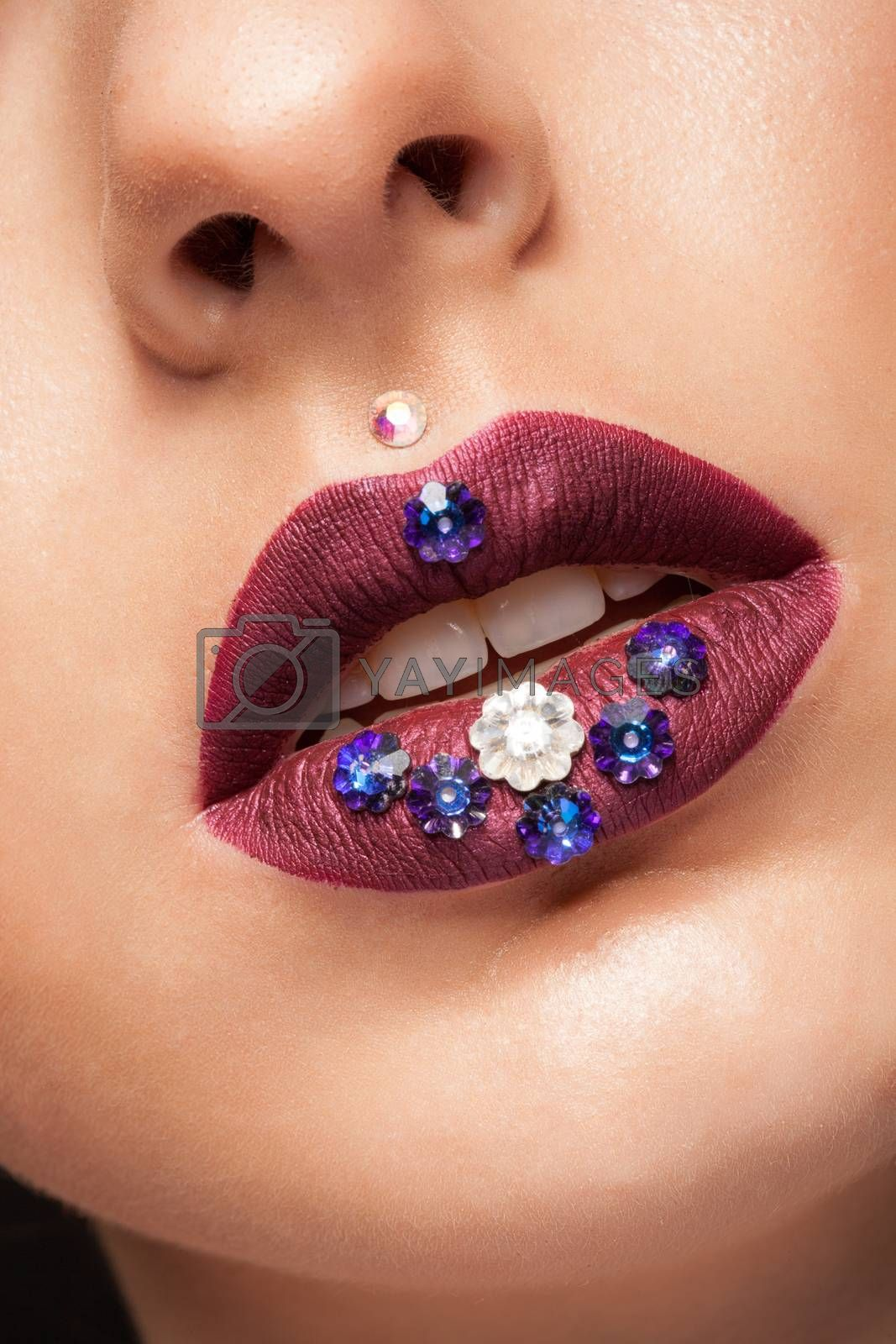 Close up of beautiful womna with mate creative lipstick and diamond flowers. Woman with mate burgundy lips. Open mouth. White teeth.