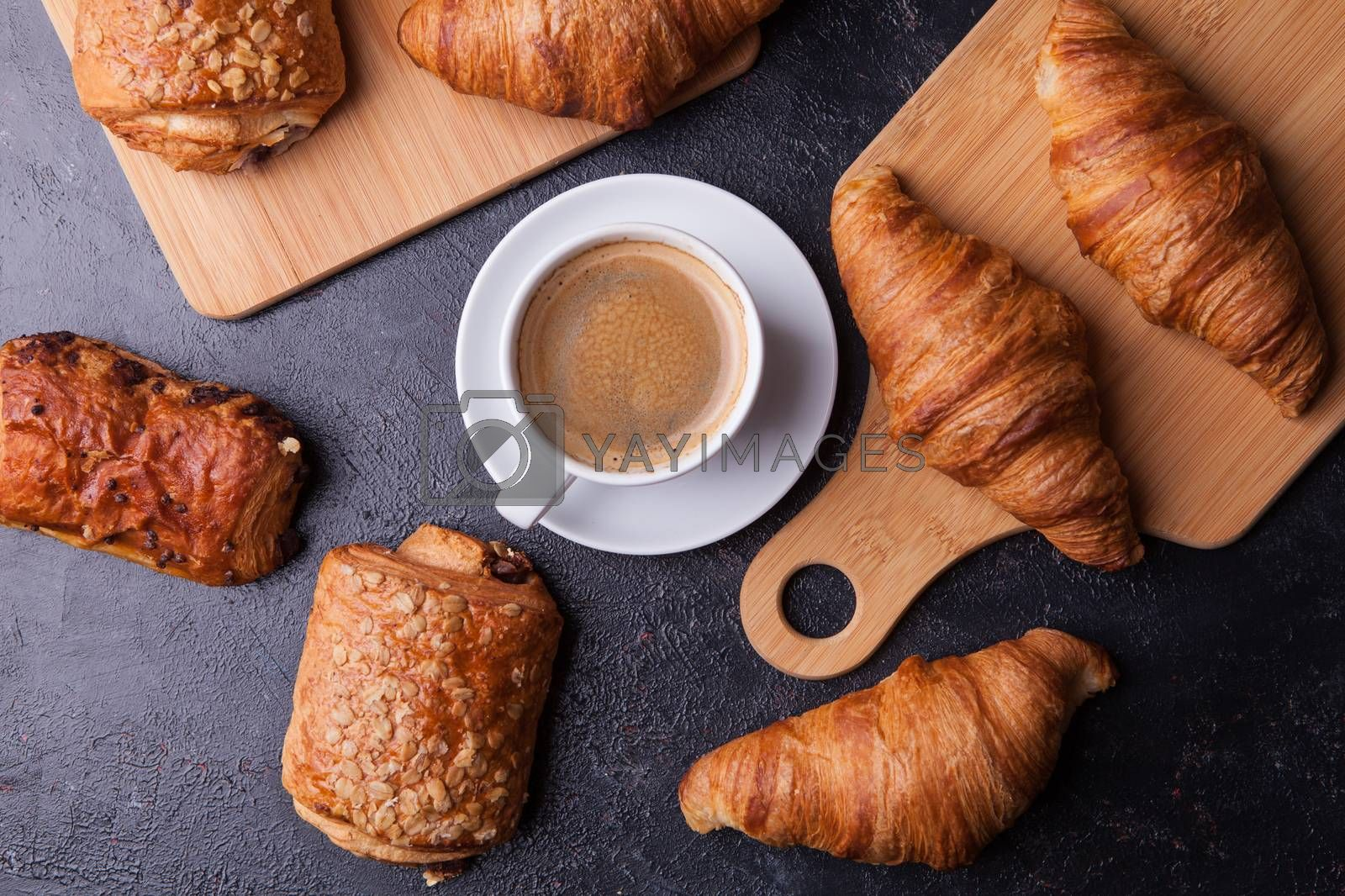 Assortment of pastries with coffee cup on wooden table background. French cuisine.