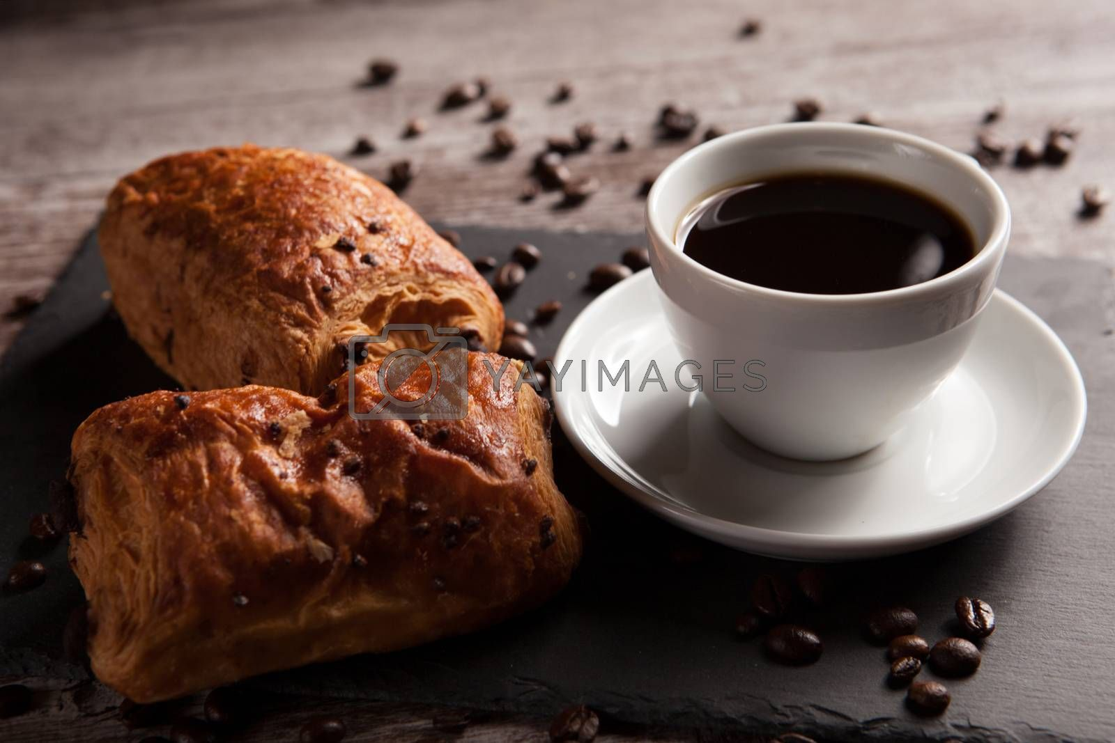 Mug of coffee with delicious pastry and spreaded beans of coffee by DCStudio