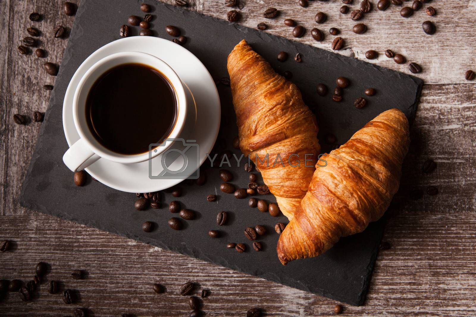 Croissant and cup of hot coffee on dark wooden table by DCStudio
