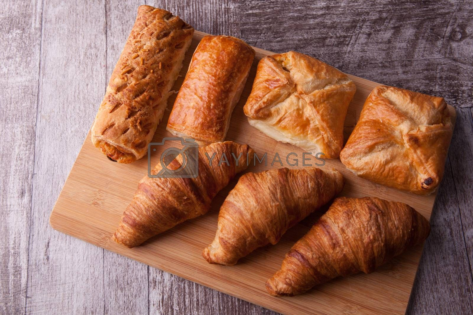 An assortment of freshly baked pastry aligned on cutting board by DCStudio