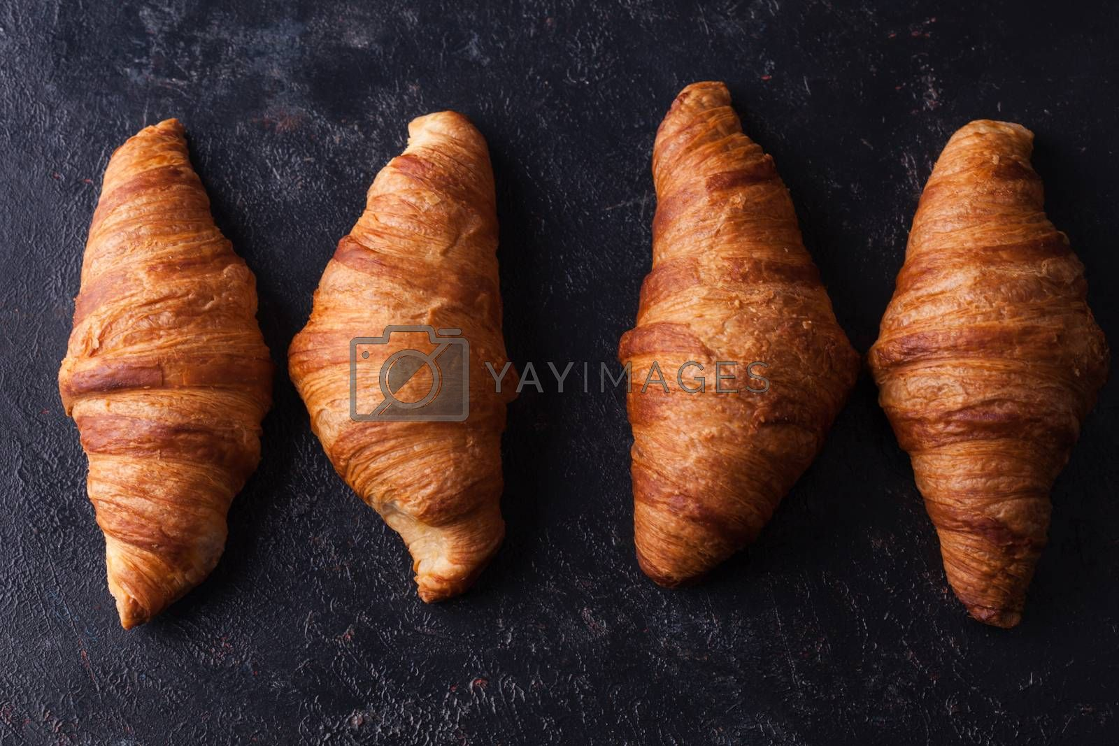 Fresh baked traditional croissants on dark wooden table by DCStudio