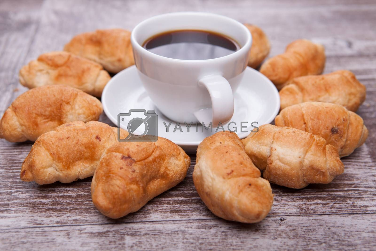Freshly baked croissants on rustic wooden table with cup of coff by DCStudio