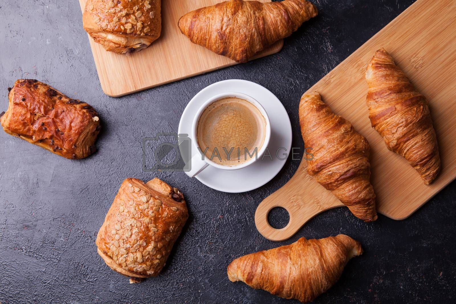 Assortment of pastries with coffee cup on wooden table background by DCStudio