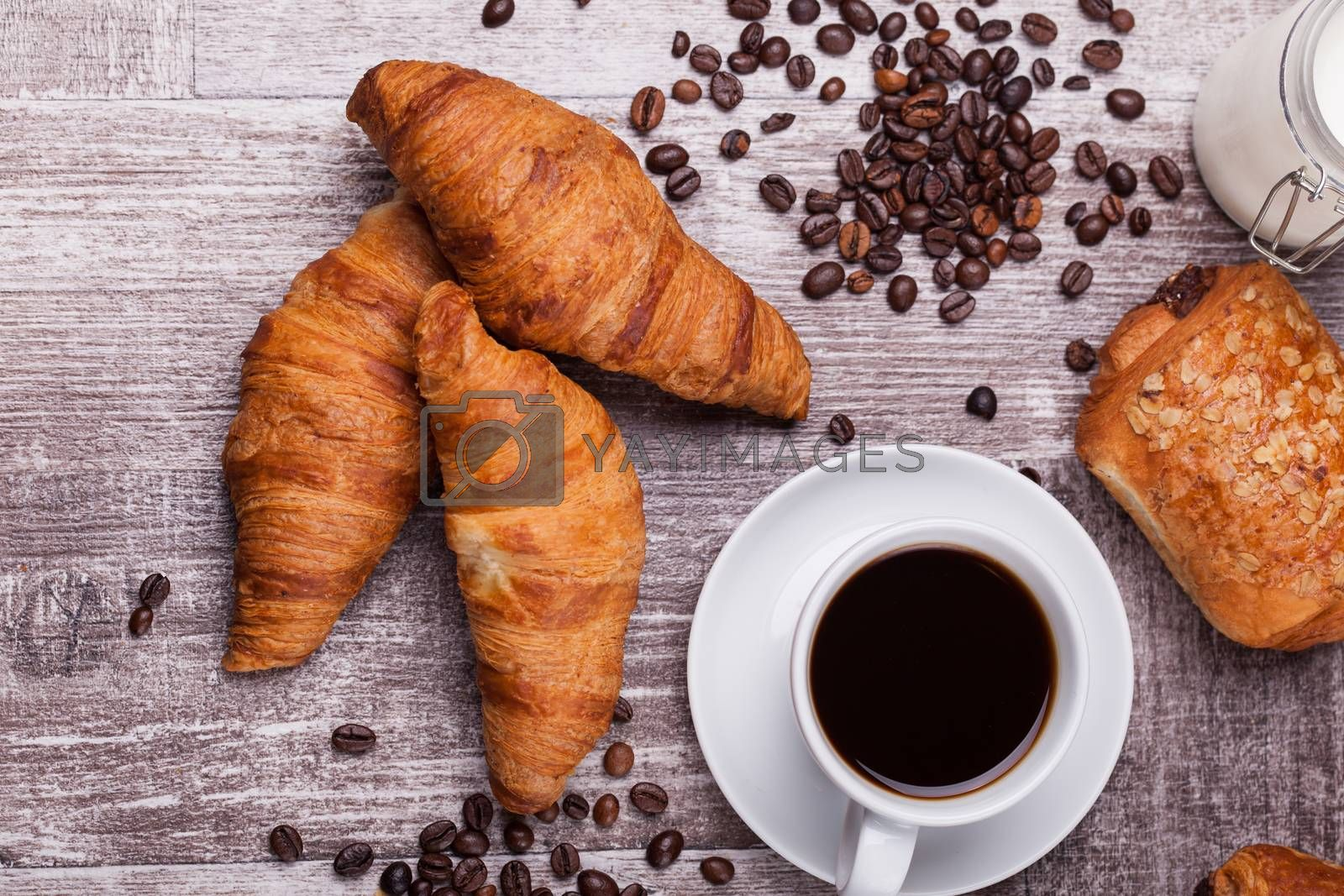 Coffee and freshly baked butter croissant on vintage wooden table by DCStudio