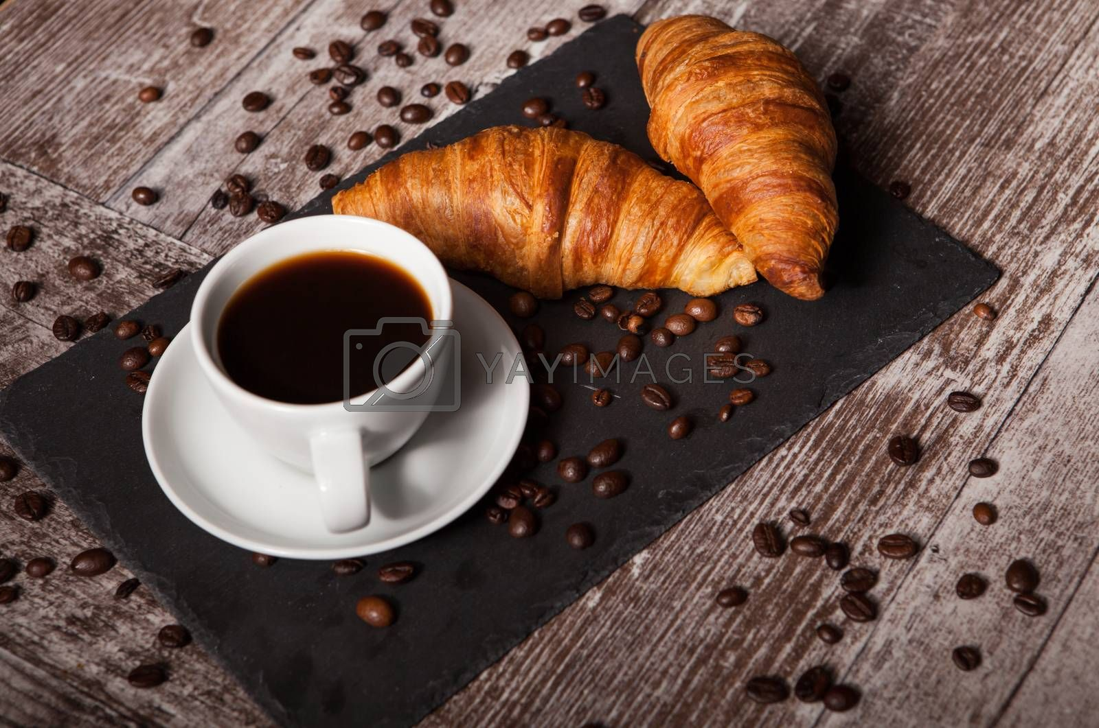 Croissant and cup of hot coffee on dark wooden table. Great breakfast.