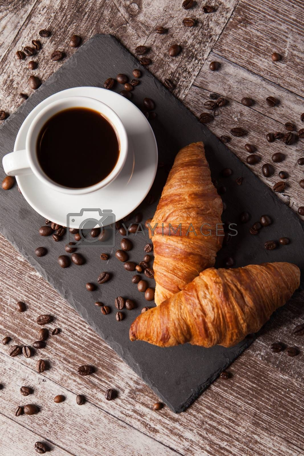 Cup of coffee and spreaded coffee beans with fresh croissants by DCStudio
