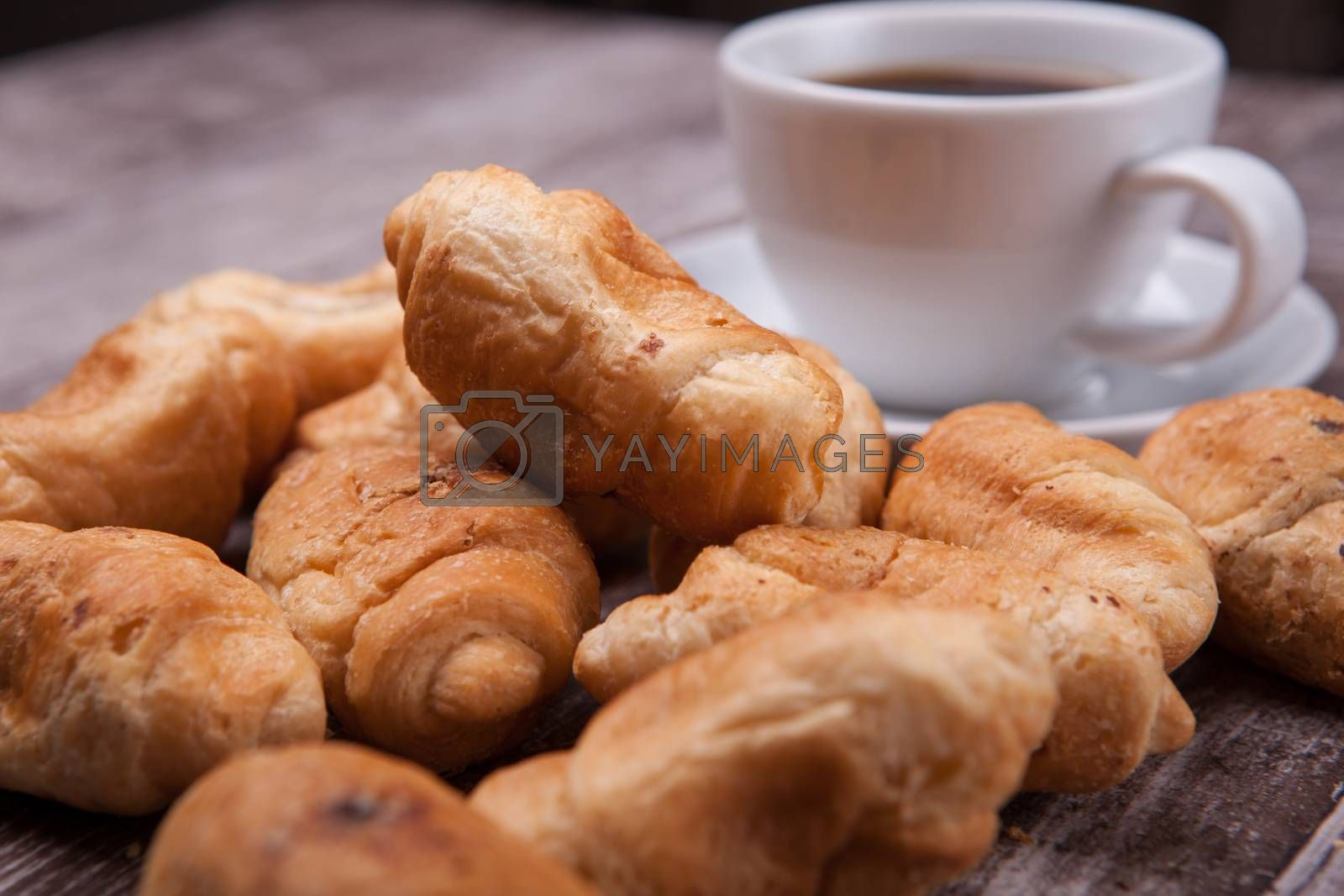 Freshly baked croissants on rustic wooden table with cup of coffee. Delicious coffee.
