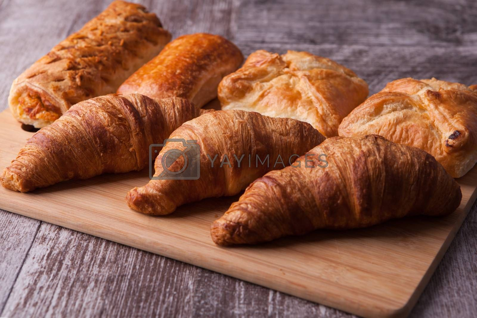 Row of fresh tasty pastry on cutting board by DCStudio