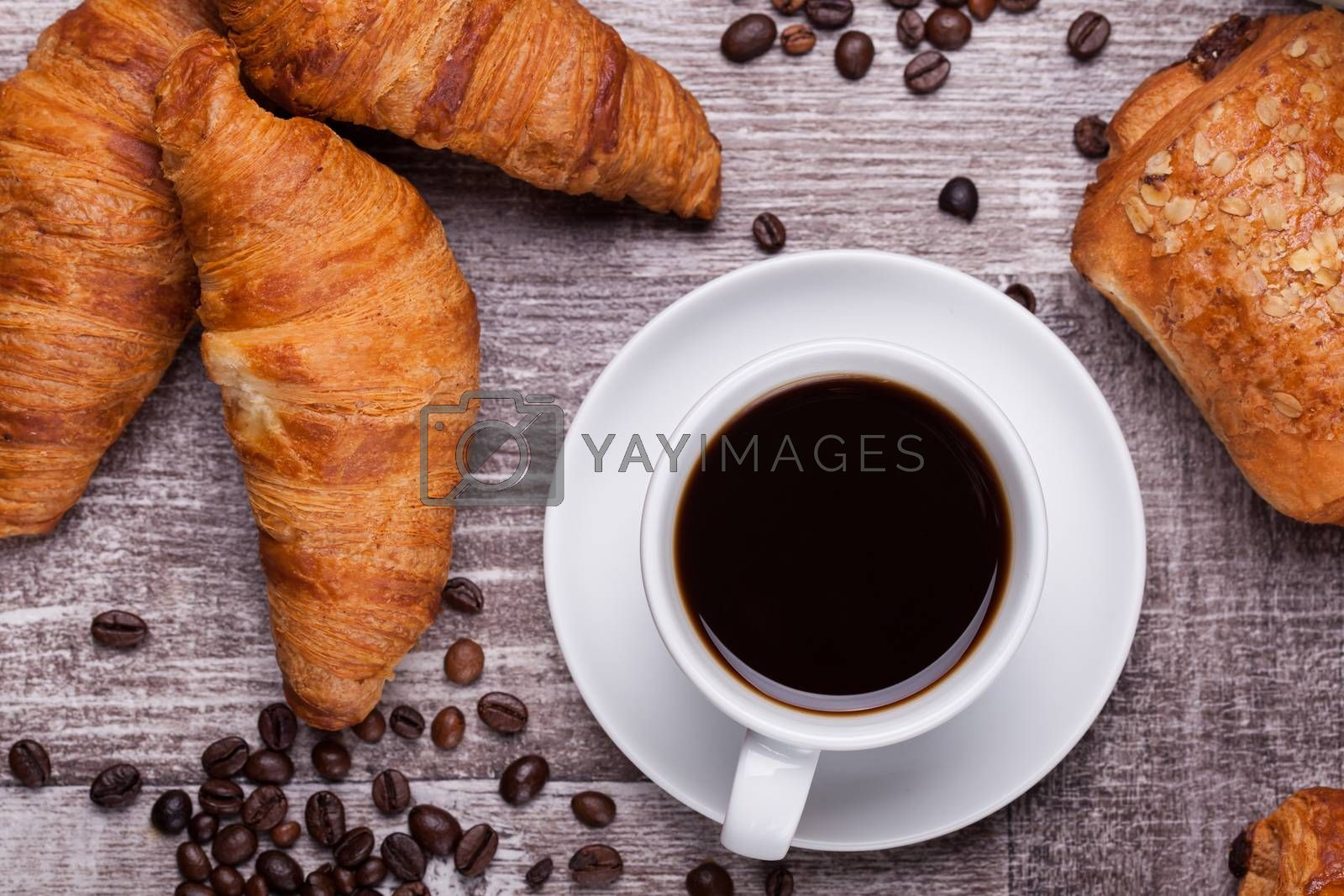 Cup of hot coffee and freshly baked croissants on dark wooden ta by DCStudio