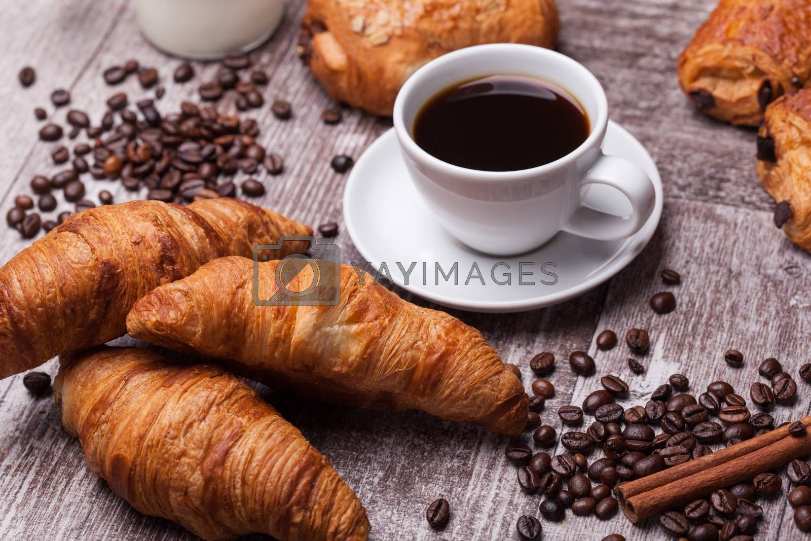 Coffee and croissant for breakfast on rustic wooden table by DCStudio