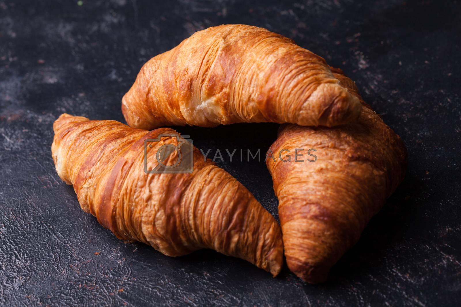 Fresh butter croissants on dark wooden table. French cuisine.