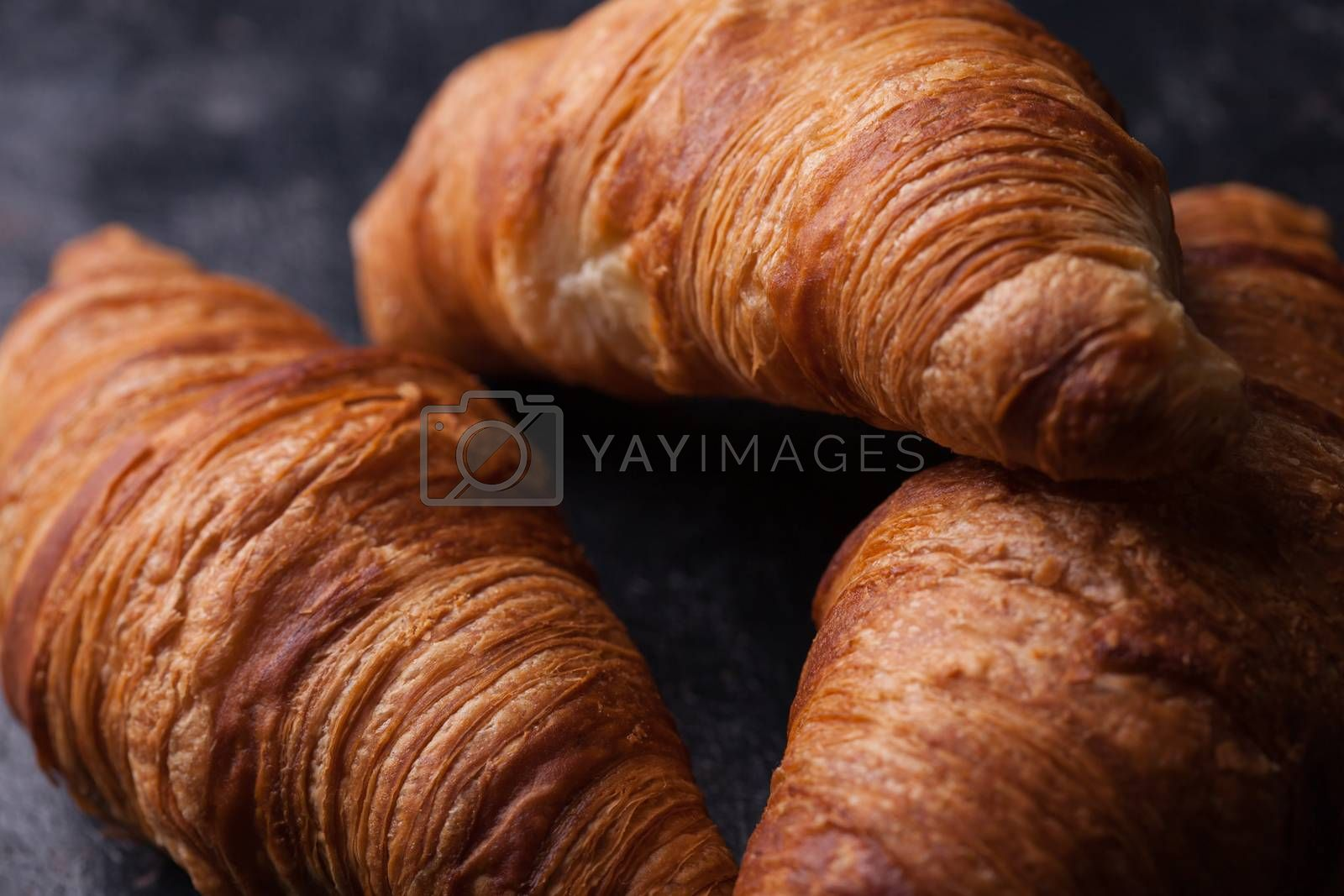Tasty french croissants on a black wooden table. Great dessert.
