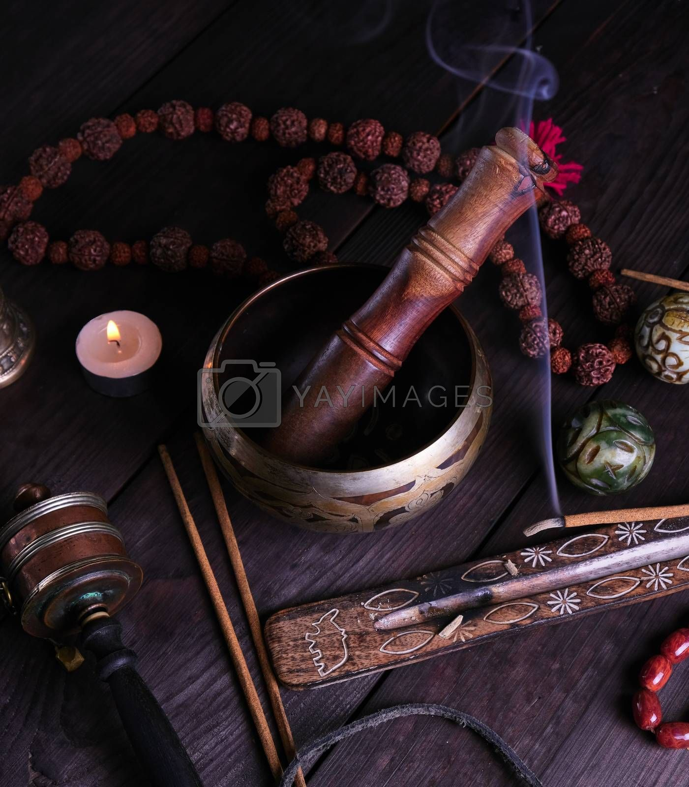 copper singing bowl and a wooden stick by ndanko