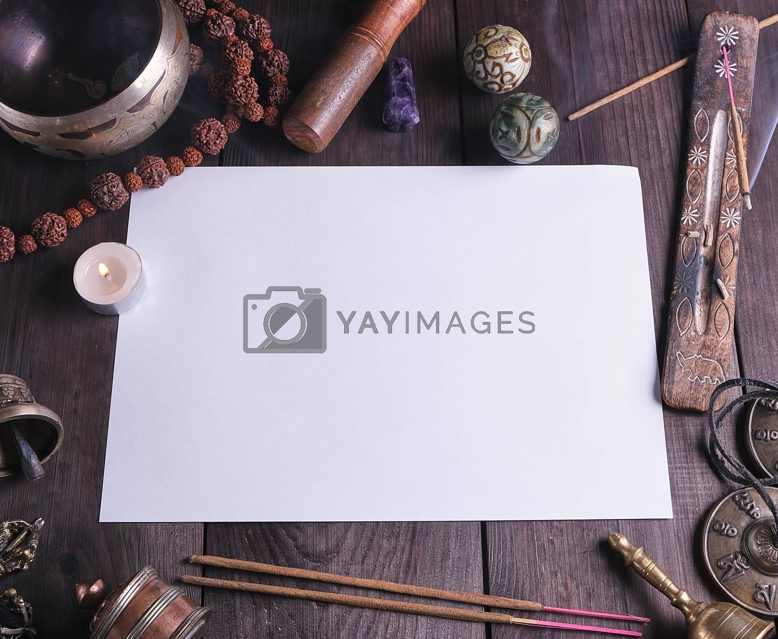 blank white sheet in the middle of religious objects for meditation, relaxation and massage on a brown wooden background