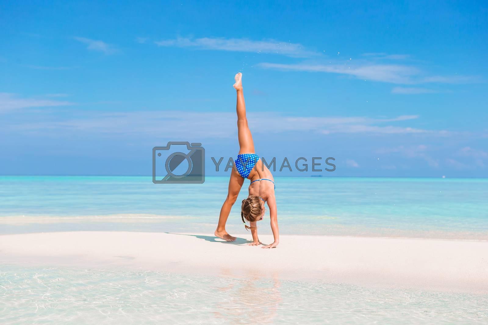Adorable girl making wheel on tropical white sandy beach