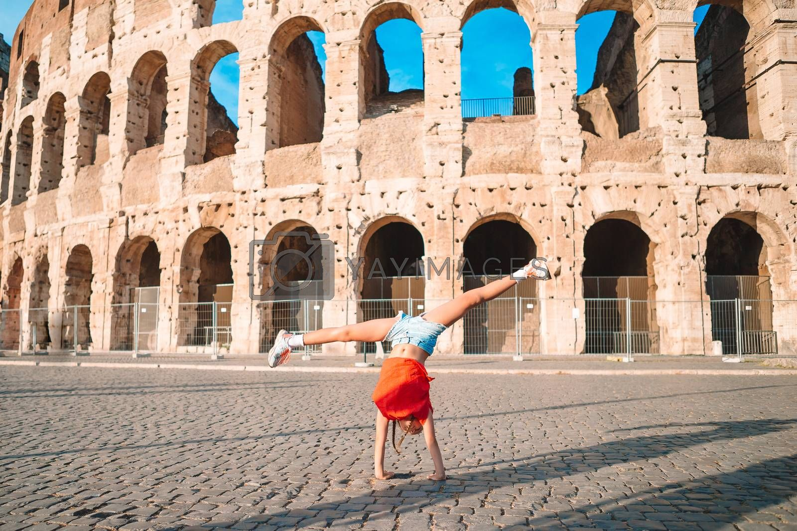 Adorable little active girl having fun in front of Colosseum in Rome, Italy