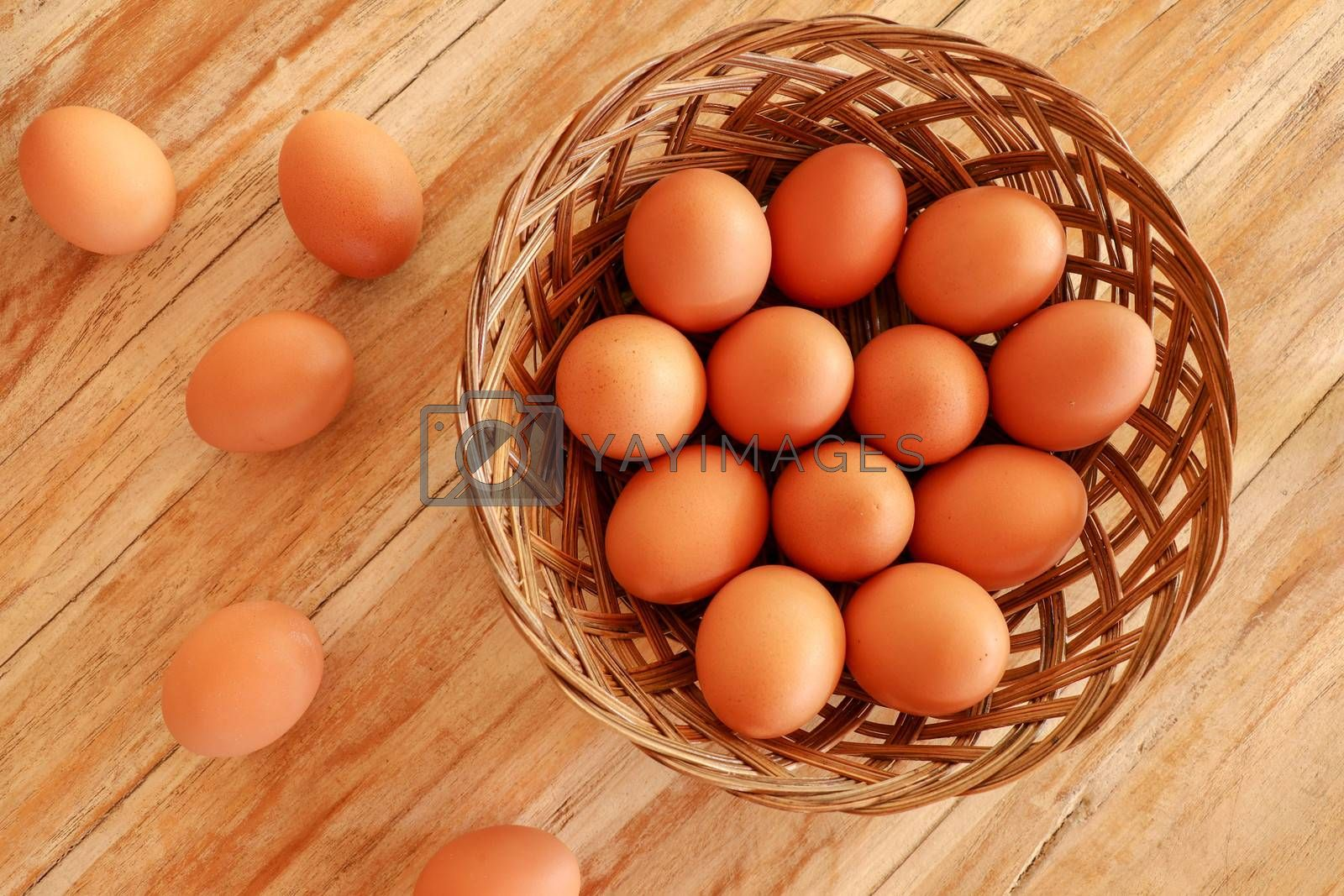 Top view of brown eggs in a wicker basket. Eggs in a wooden basket on a wooden table.