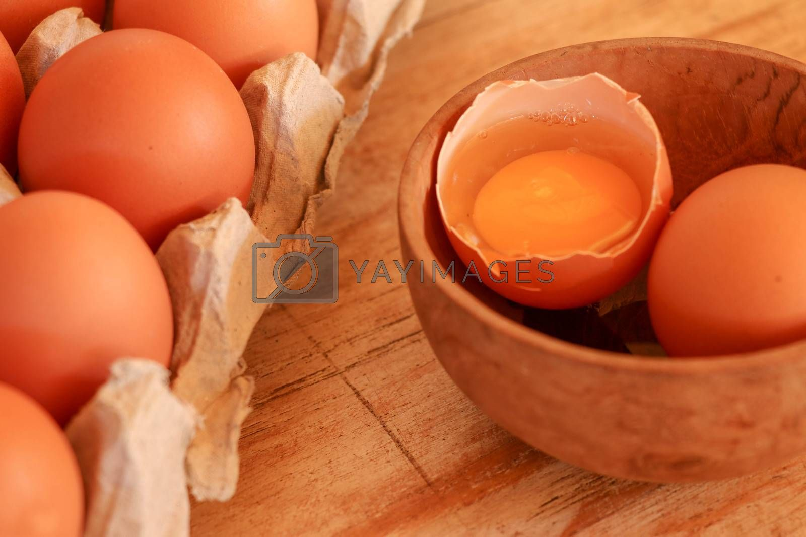 Cracked egg in bowl and egg shells on wooden table.